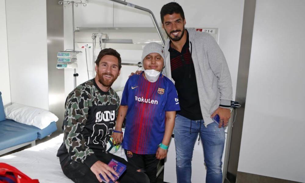 Luis Suárez e Messi com uma criança hospitalizada