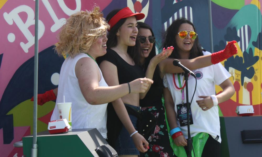 Festivaleiras participam no karaoke da McDonald's ao som do jingle do Big Mac em celebração aos seus 50 anos de existência